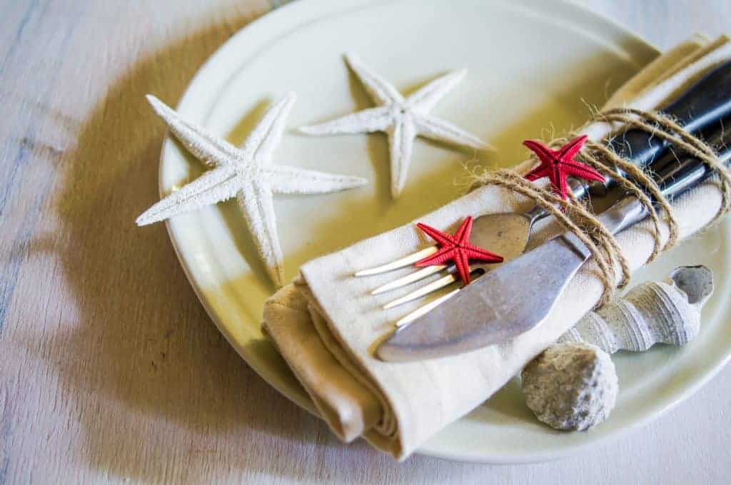 Nautical Table Decor - white plate, white star fish, white napkin and untensils tied with jute rope and adorned with red star fish.