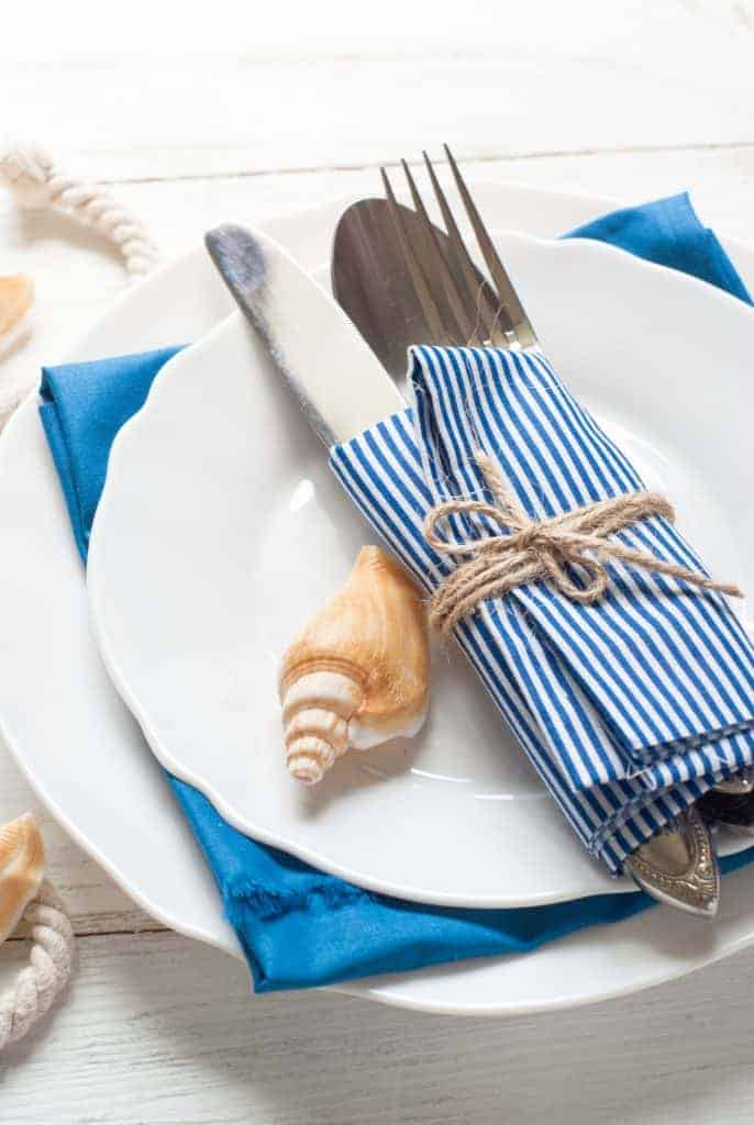 White plates with blue and white striped napkin bound with jute string and decorated with a sea shell