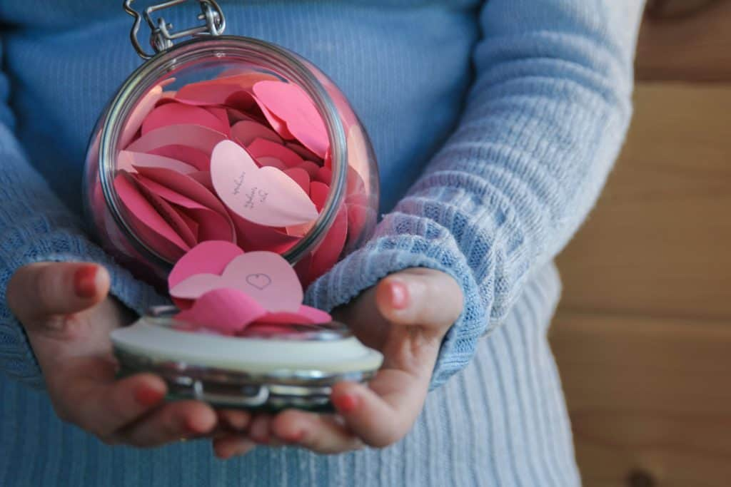 A glass mason jar filled with paper hearts where kids have written notes to mom about how much they love her on Mother's Day.