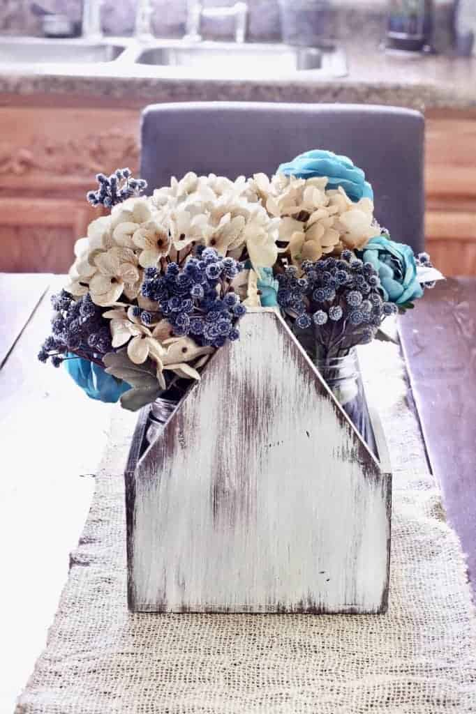 Easy Spring Table Setting Idea: white wooden tool box filled with blue flowers in mason jars.