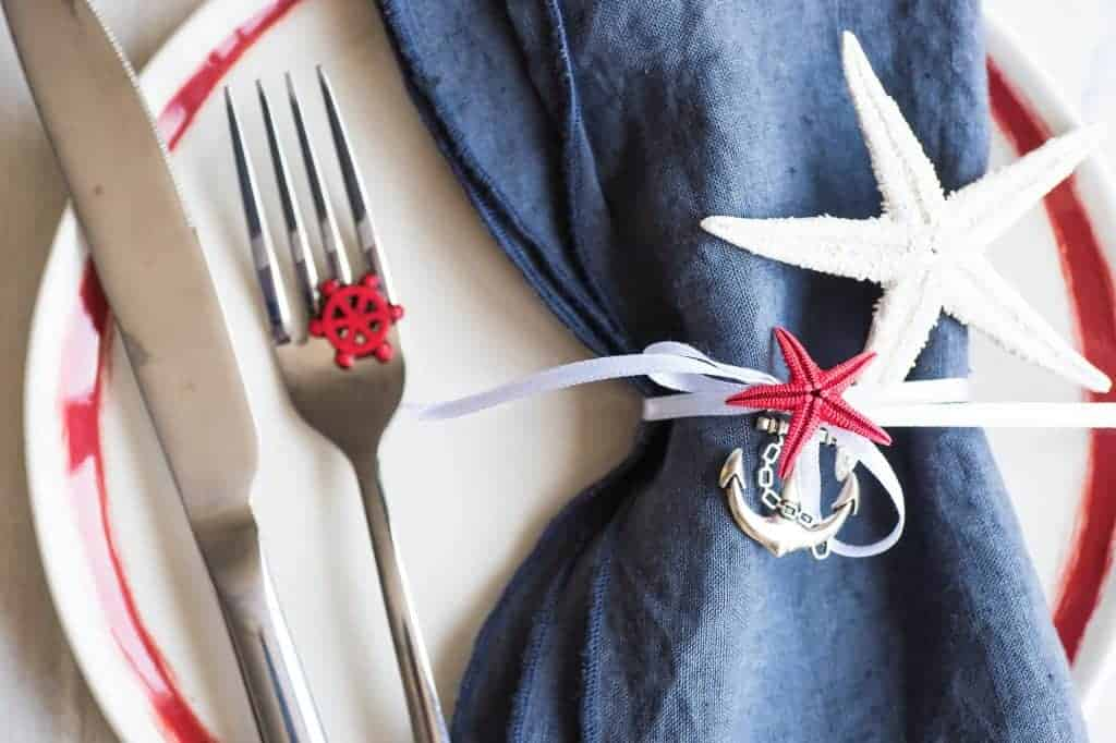 Nautical Table Settings - decor idea. Red, white and blue. White plate with red rim, blue linen napkin tied with white ribbon and adorned with an anchor charm, and star fish.
