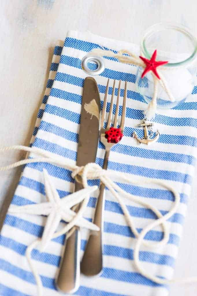 Nautical Table Setting decor - Blue and white napkin with grommet hole and tied with a white craft rope. Glass with unscented white candle.
