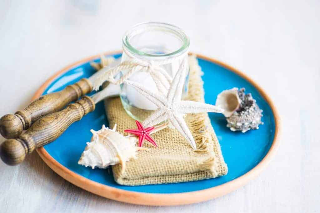 Nautical table settings - Blue plate with orange rim with jute napkin, glass candle holder with candle, and wood utensils. Shells and starfish.
