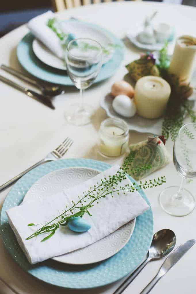 Pretty Easter table setting idea. Blue plates topped with white plates and white napkins with natural greens and a blue decorative egg.