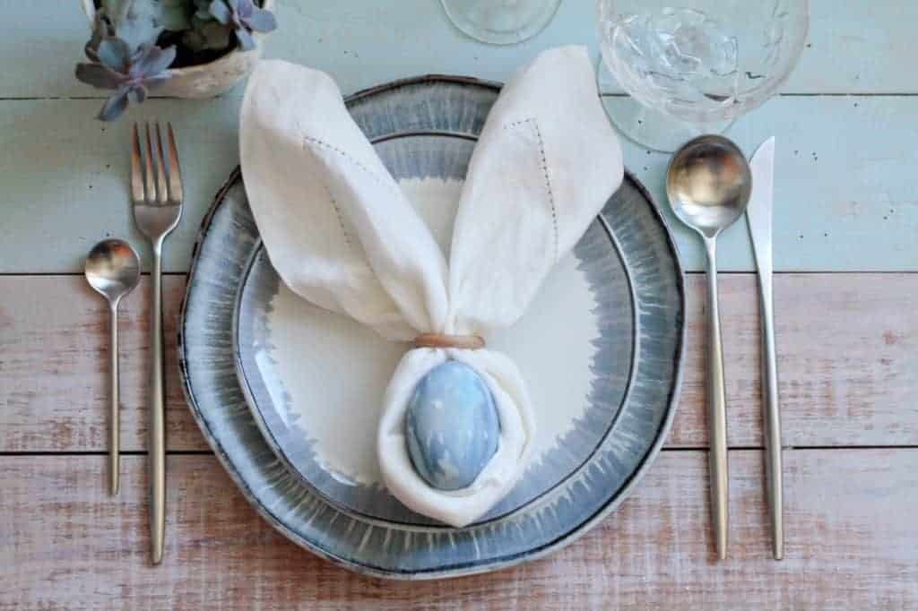 Spring table settings idea - blue rimmed plates with a napkin that is gathered around a blue egg to look like bunny ears.