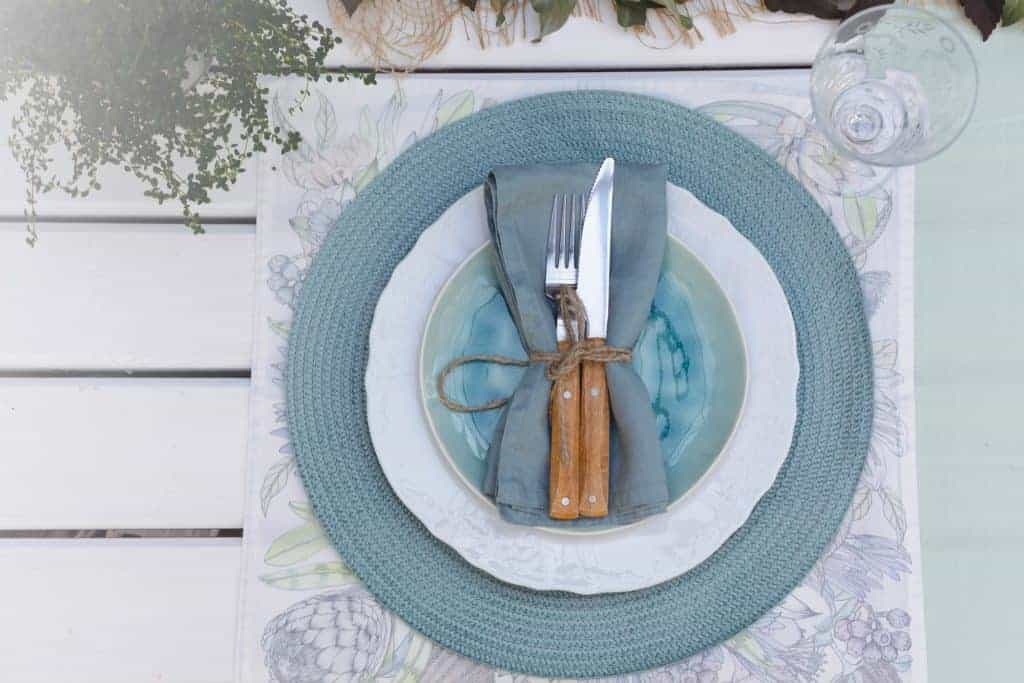 Simple spring table setting with floral placemat in blues and purples, topped with a blue charger, and wooden utensils wrapped in a blue napkin with twine.