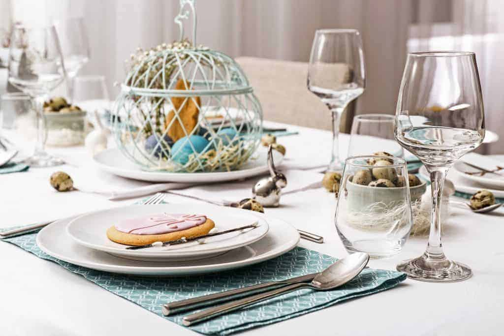 Easy Easter Tablescape idea - spring table setting with a wire basket holding Easter Eggs and Easter grass in the middle and Easter Egg cookies on top.