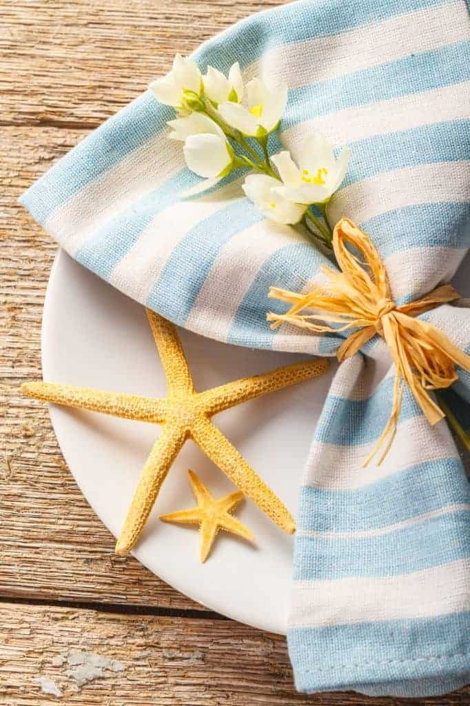 Nautical table setting decor idea: light blue napkin tied with raffia ribbon and adorned with flowers. Sea stars on the side.
