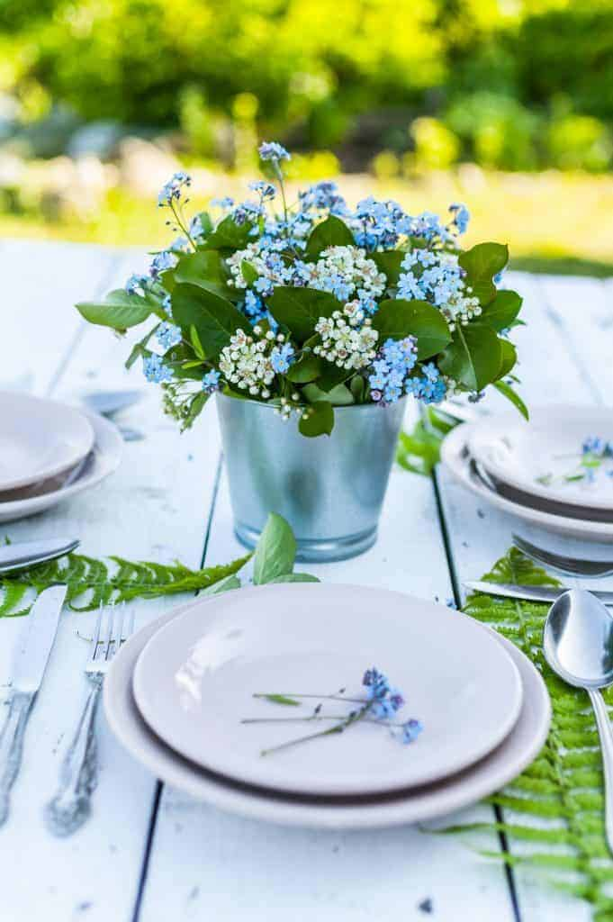 Pretty blue and white flowers in a tin planter used as a centerpiece for a spring table setting.  Fern leaves also decorate the table.