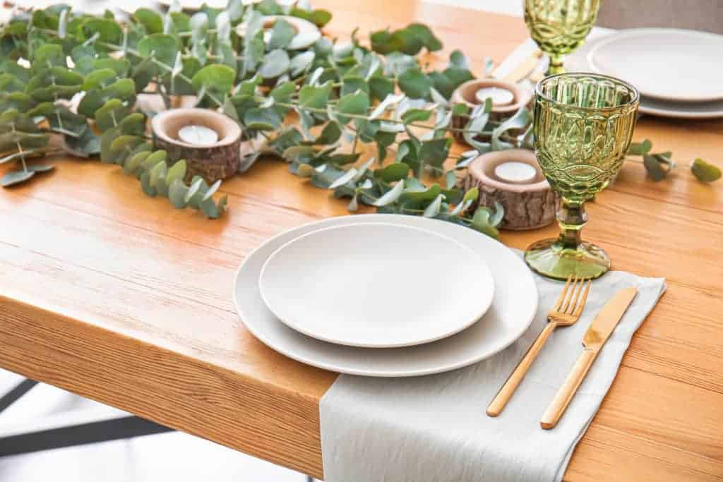 More formal spring dining table set up with eucalyptus, and tea light candles in bark candle holders.