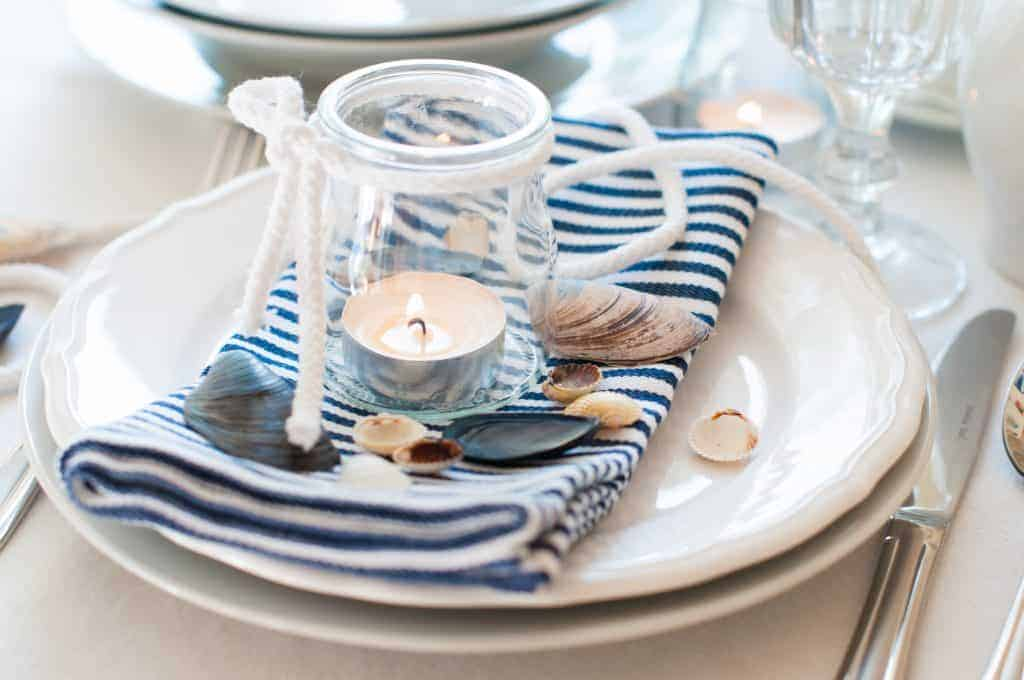 Nautical Table Decor: White scalloped plates with a blue and white striped napkin, a small glass candle holder with a tea light, and shells.