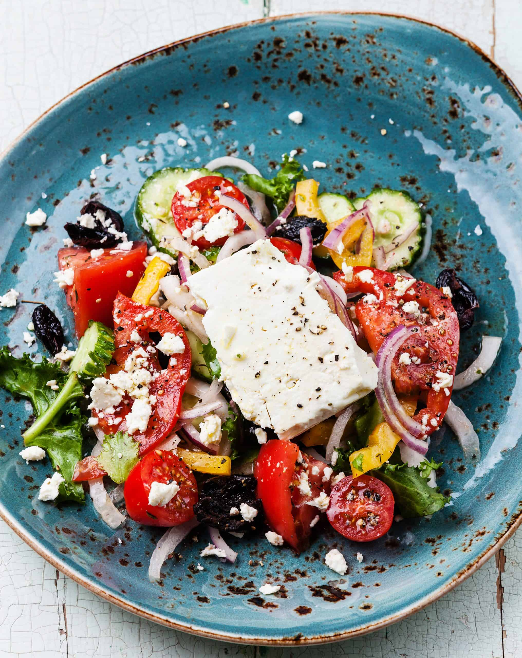 Salad with feta cheese, tomatoes, red onions, black olives on a blue plate.