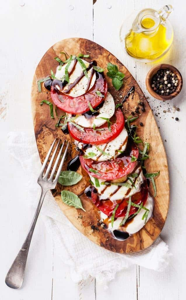 Easy Summer Salad - fresh mozzarella, basil, and tomato with balsamic reduction on a cutting board for serving.