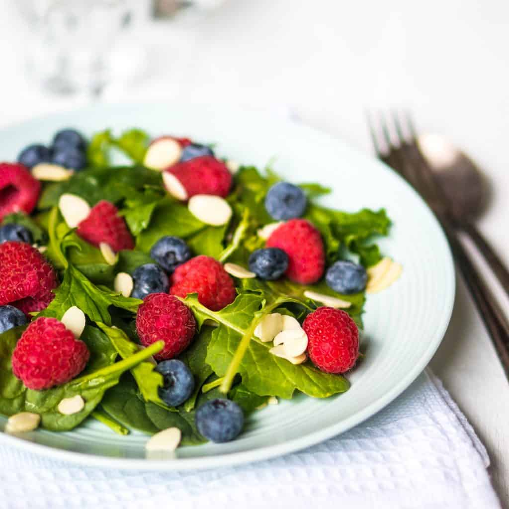 Green salad with fresh blueberries, slivered almonds, and fresh raspberries.
