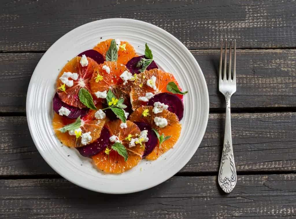 beautiful, easy summer salad make with bright orange oranges, roasted, sliced beets, mint, and crumbled farmer's cheese
