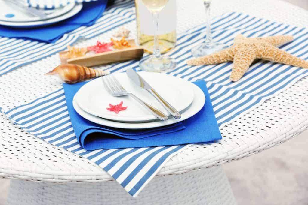 Nautical Table Decor idea: White table with blue and white striped placemat, a blue napkin and white dishes with sea stars and shells on table.