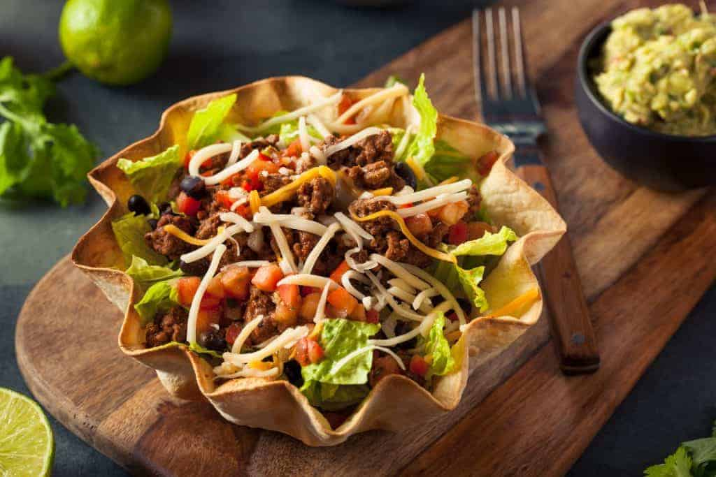Easy Summer Salads for a crowd.  Taco shell with taco meat, cheese, lettuce, black olives, tomatoes.