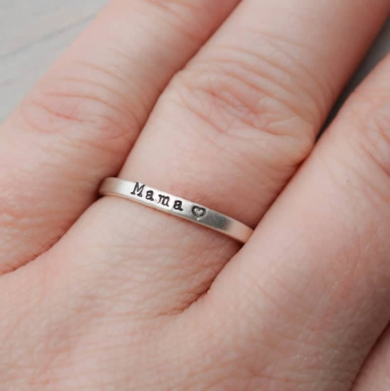 A beautiful silver ring from Simpli Stamped Jewelry with the word Mama and a heart stamped on it as a gift for Mother's Day