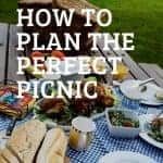 A picnic table with a blue checkered cloth and picnic food. A wicker picnic basket is also on the table.