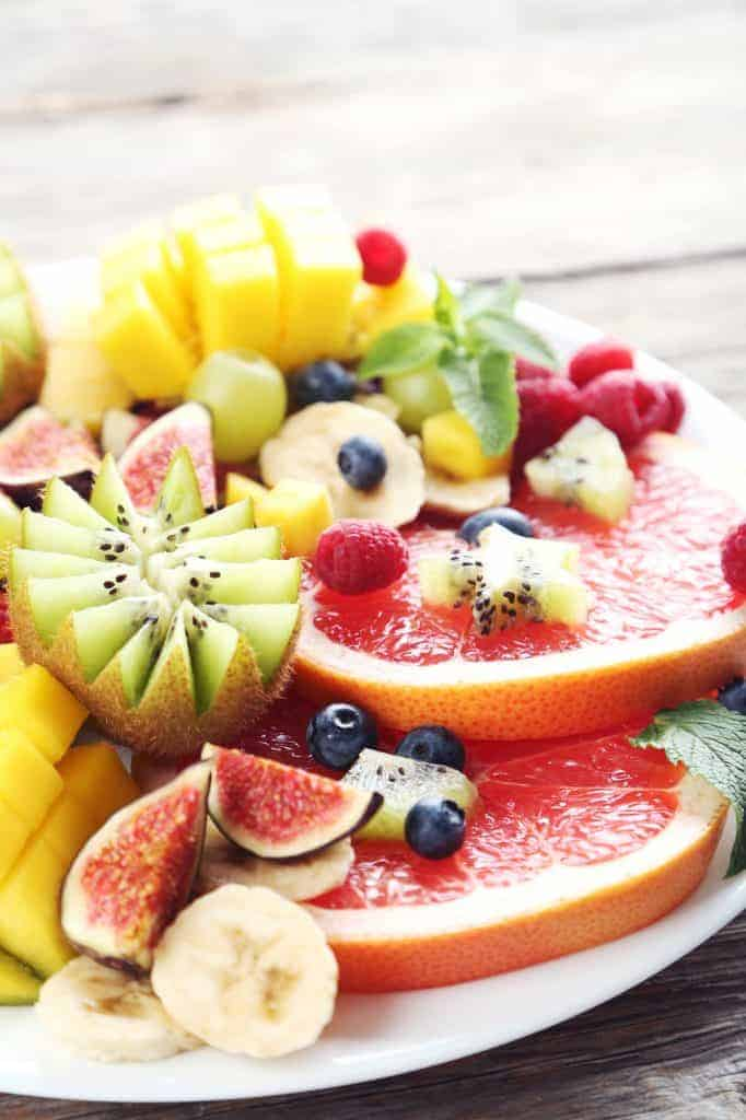 Fruit platter with grapefruit, mango, fig, bananas, kiwi, and blueberries. Kiwis are cut into pretty shapes