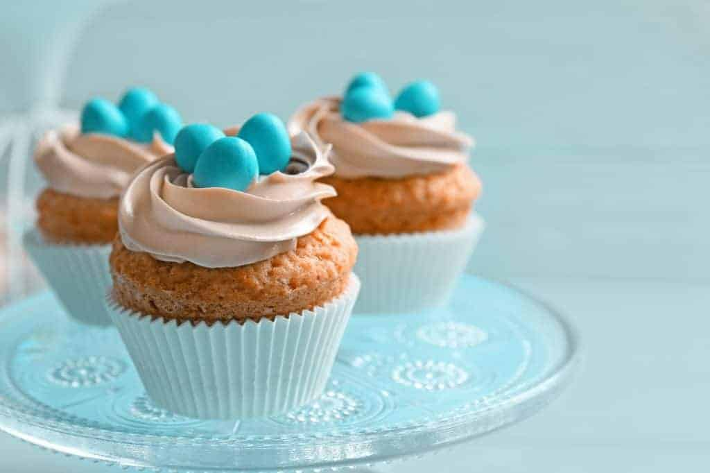vanilla cupcakes in a white paper topped with chocolate icing and blue robins egg candies