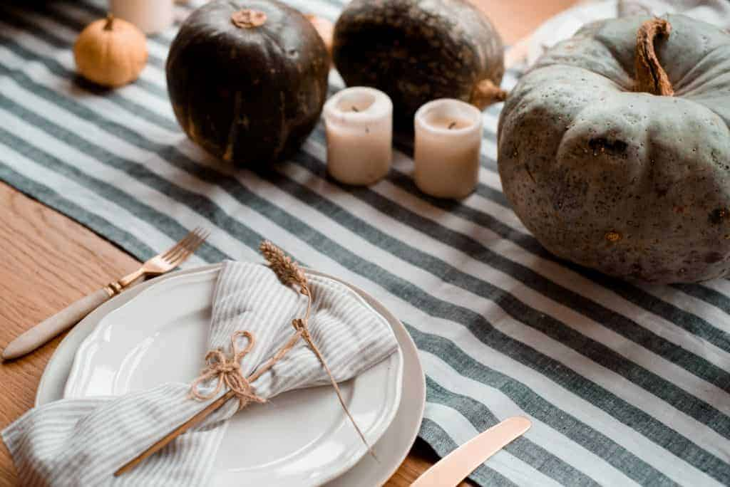 Simple striped runner with darker green colored gourds and candles. Place settings have striped, muted napkins wrapped in twine with a sprig of wheat. Gold flatware.