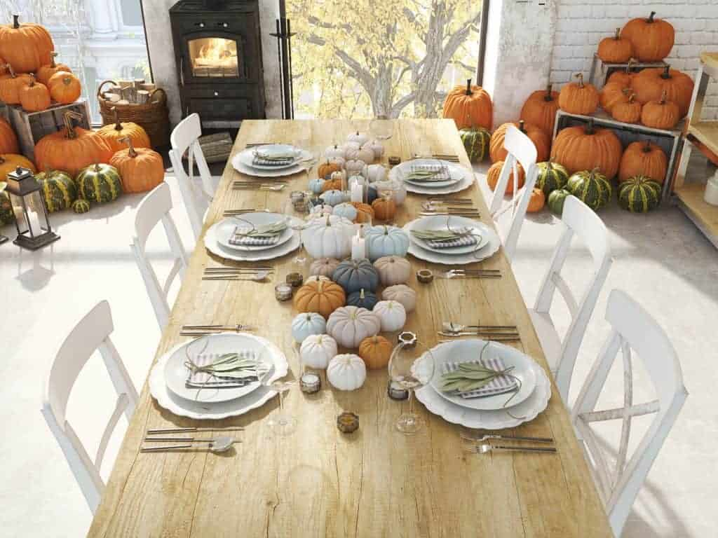 Fall tablescapes & place settings. Pretty farmhouse table with white plates, striped gray napkins with a sprig of sage on each place setting. The featured centerpiece is many different muted colored pumpkins with candles.