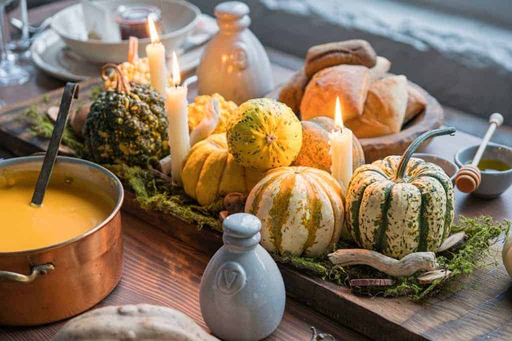 Fall tablescapes & place setting idea: wooden table with gourds and candles in the middle.