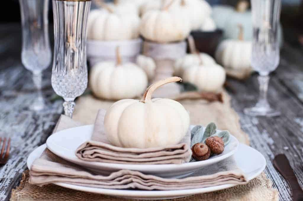 Fall Tablescapes & Place Settings Inspiration - White plates with light brown napkins topped with a white pumpkin, sage leaves an acorn on a white farmhouse table with white pumpkin centerpiece.