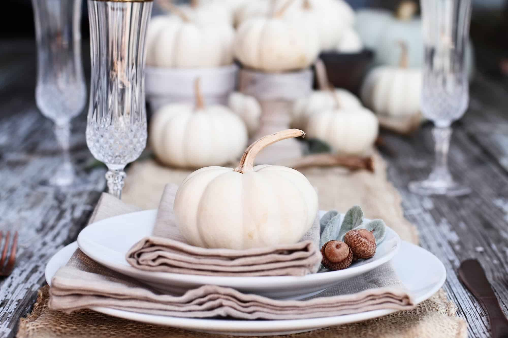 Beautiful fall tablescape with white dishes, pumpkins, and natural color napkins