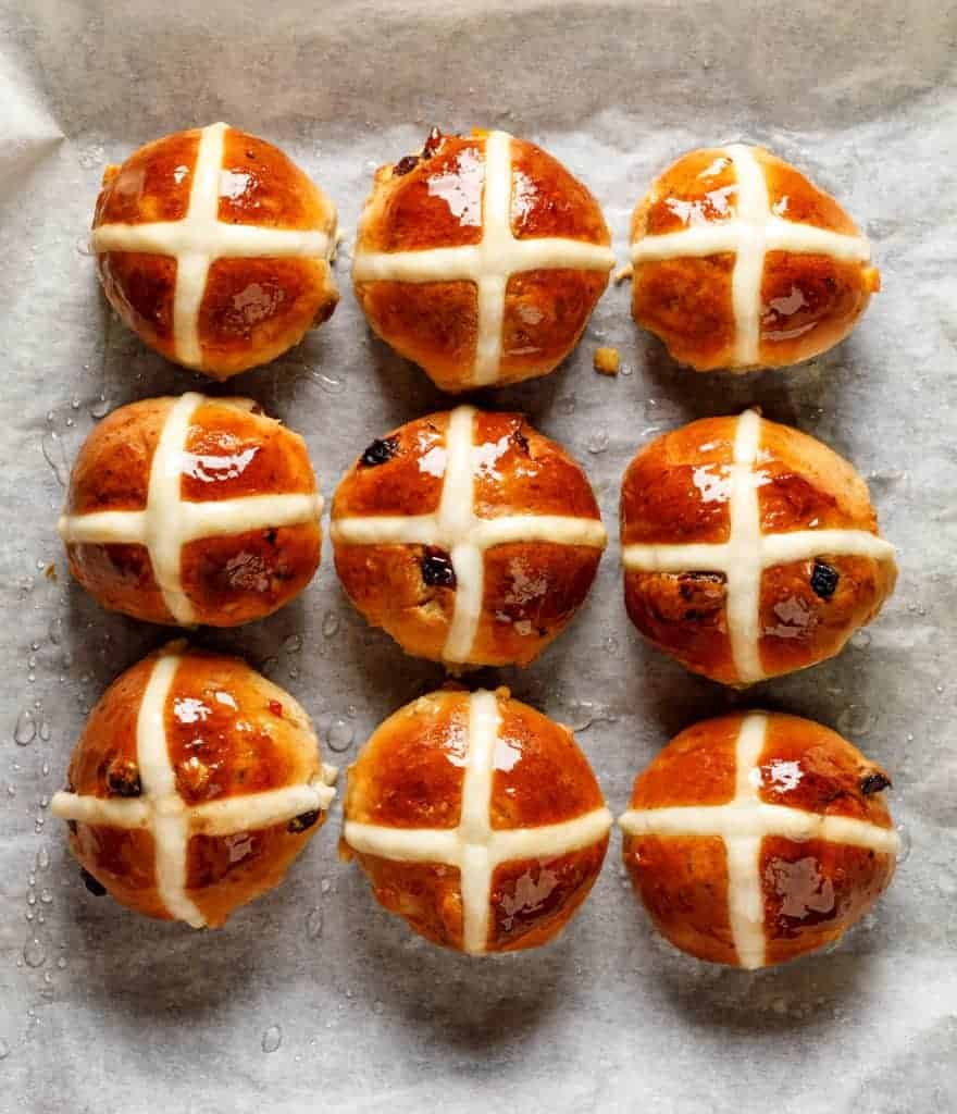 Hot cross buns - brown buns with a cross on top sitting on parchment paper
