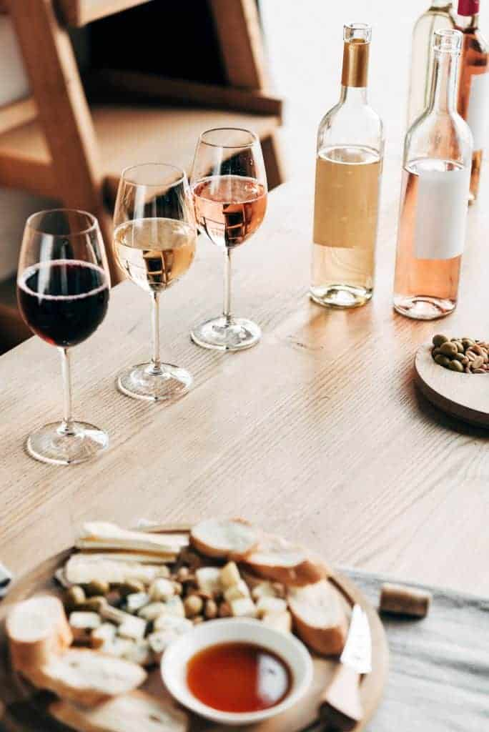 A wine tasting party table set up with three different glasses of wine and bottles along with a simple snack board.