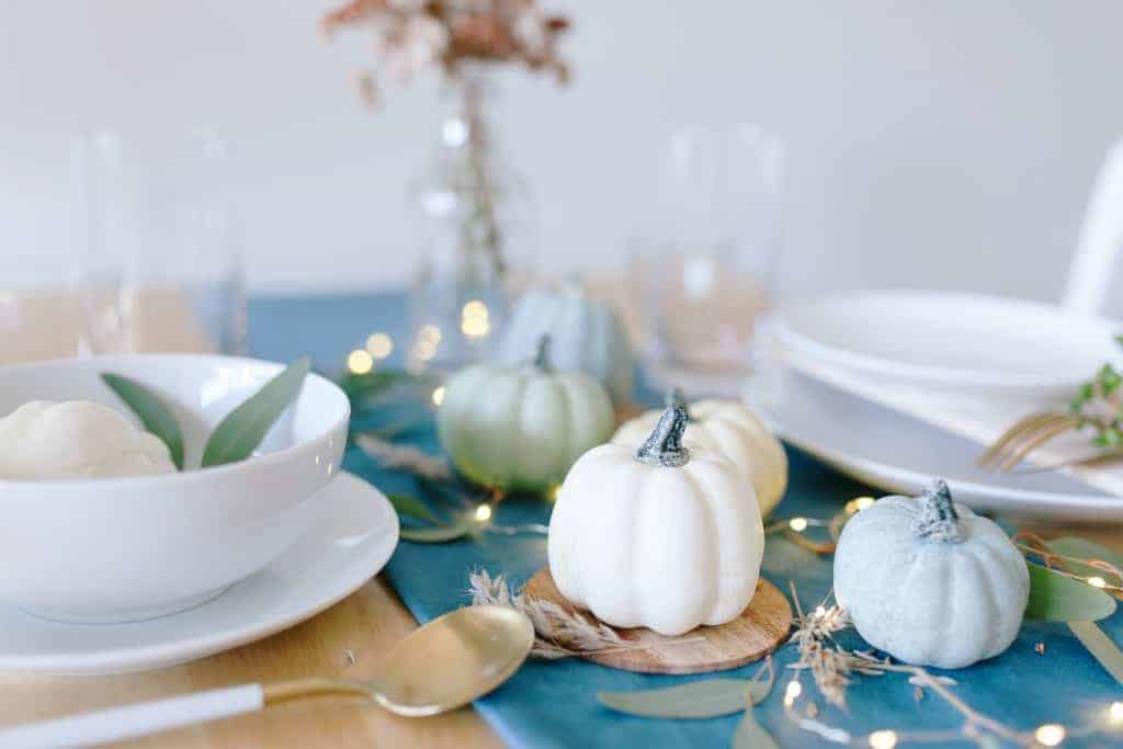 Fall tablescapes & place settings - Simple table with blue runner, white dishes, small pumpkins, and sage leaves.