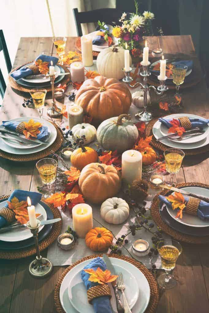 Beautiful fall table. Wooden table with simple linen runner. Pumpkins of different colors on top of foliage, and gathered around different sized candles. Woven placemats topped with white dishes and blue napkins adorned with a leaf.