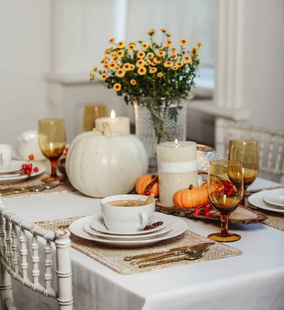 Fall place settings & centerpieces: white tablecloth with natural colored placemats, white dishes, amber colored glasses and gold flatware. Large white pumpkin with white candles and a bouquet of orange mums. along with a wood slab.