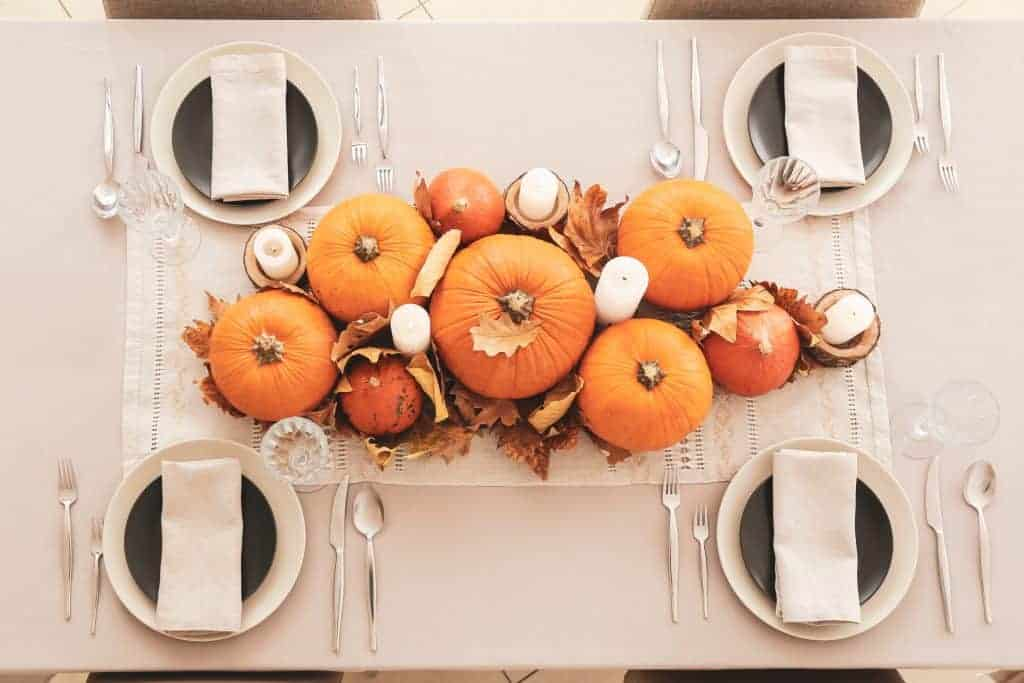 Fall tablescapes & place settings. Ecru tablecloth with matching plates topped with darker plates. Silver flatware. Pumpkins, candles, and foliage on a smaller scale as a centerpiece.