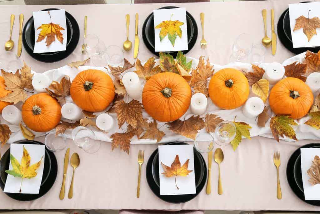 White tablecloth with black dishes adorned with a white napkin and a leaf at each place setting with gold flatware. A lighter white runner with five pumpkins, candles, and foliage go down the center of the table.