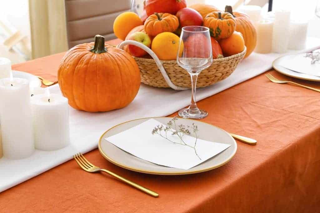 Fall tablescapes & place setting ideas: Simple orange tablecloth with a white runner. Candles and a basket of pumpkins with white/gold rimmed dishes and gold flatware.