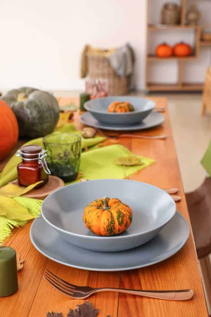 Fall Tablescapes & Place Setting inspiration. Blue/gray plates and bowls at each place setting with a green table runner in the middle and darker toned pumpkins. Green glassware.