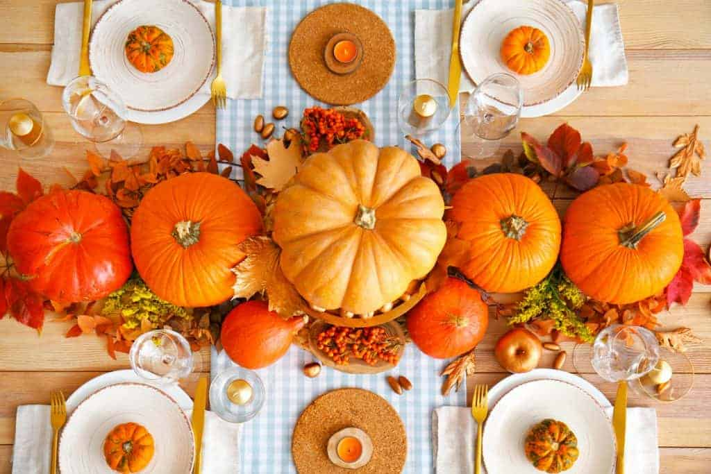 Idea for fall centerpiece - five large, orange pumpkins sit on top of fall foliage and a light blue and white runner placed width wise across the table. There are white plates and a mini pumpkin at each place setting with gold flatware.