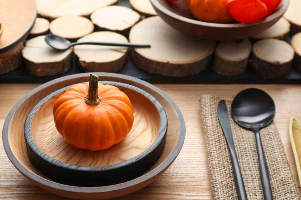 - wood table with wood dishes and jute napkin. Iron colored silverware and slices of wood down the center of the table. Mini orange pumpkins on each place setting.