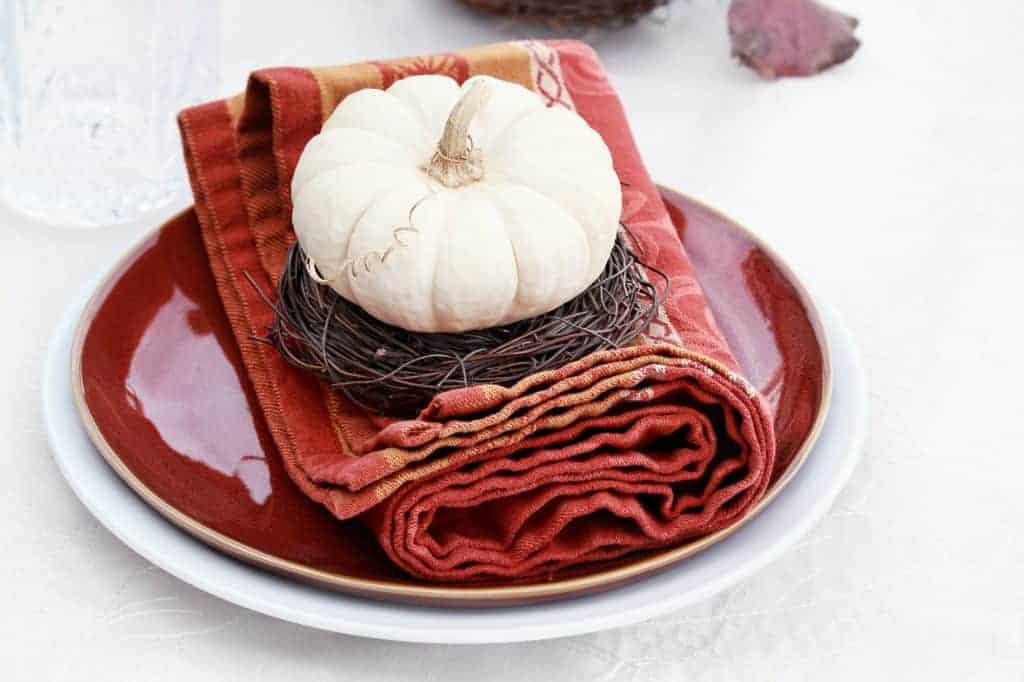 Fall tablescapes & place settings. White tablecloth with white dish topped with dark red dish and a red/orange napkin. Natural twine under a white pumpkin.