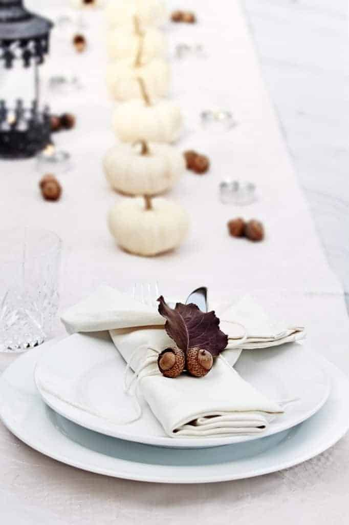 White table with a simple row of small white pumpkins down the center with candles and acorns. White dishes with a white napkin and acorns with a leaf at each place setting. A black lantern is in the middle of the table.