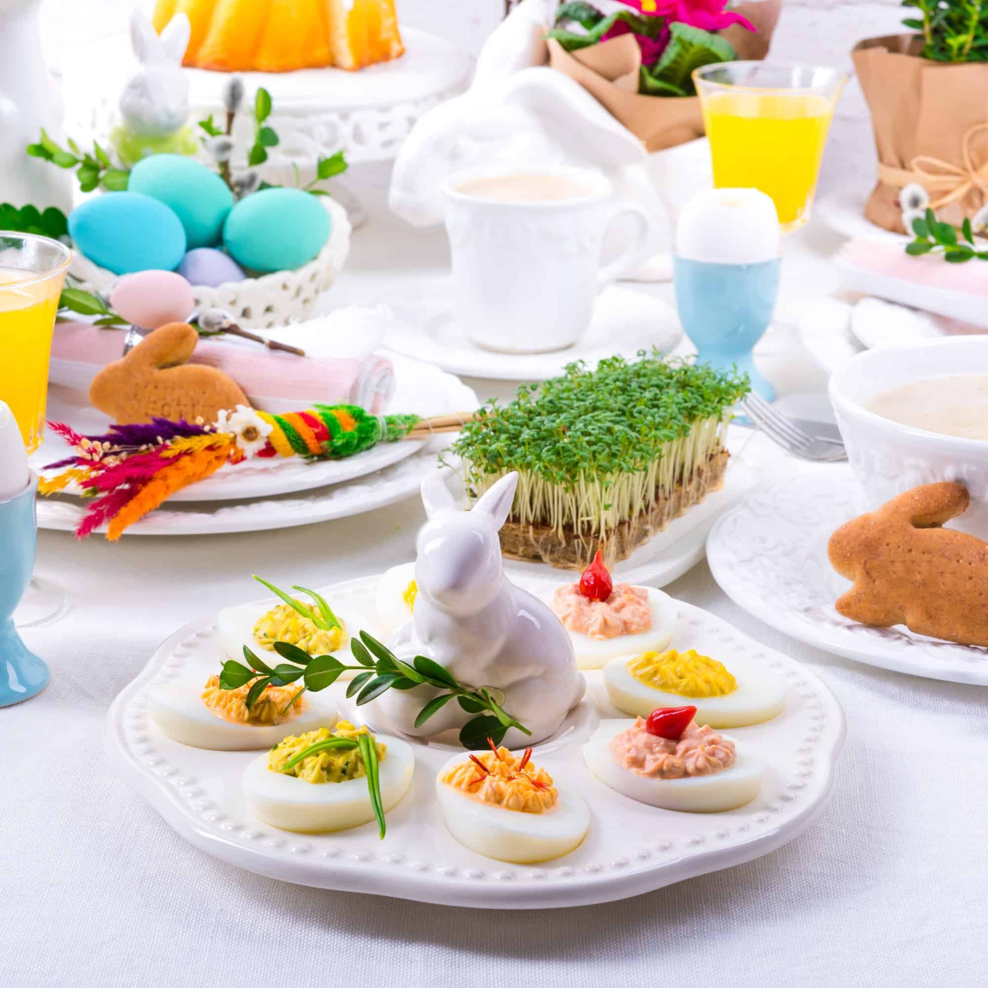 Easter Brunch table set with Easter decorations like a white bunny, deviled eggs, blue dyed Easter eggs.
