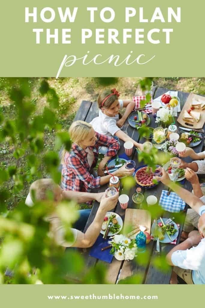 Friends gather at a picnic table in a wooded area. The table has picnic food, and drinks.