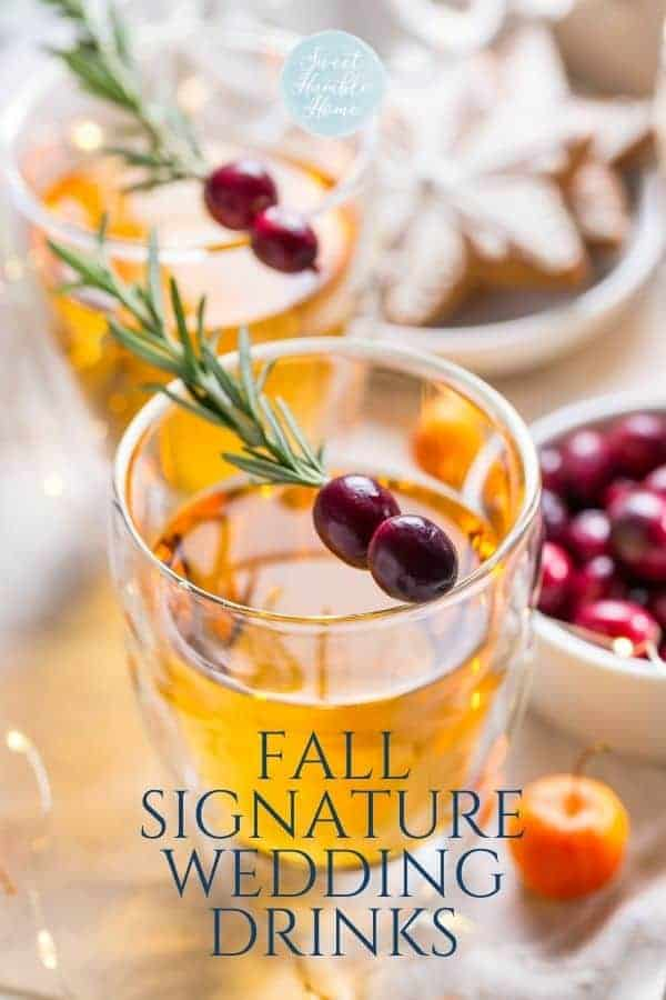 Fall inspired signature cocktail with cranberry and rosemary on a table.