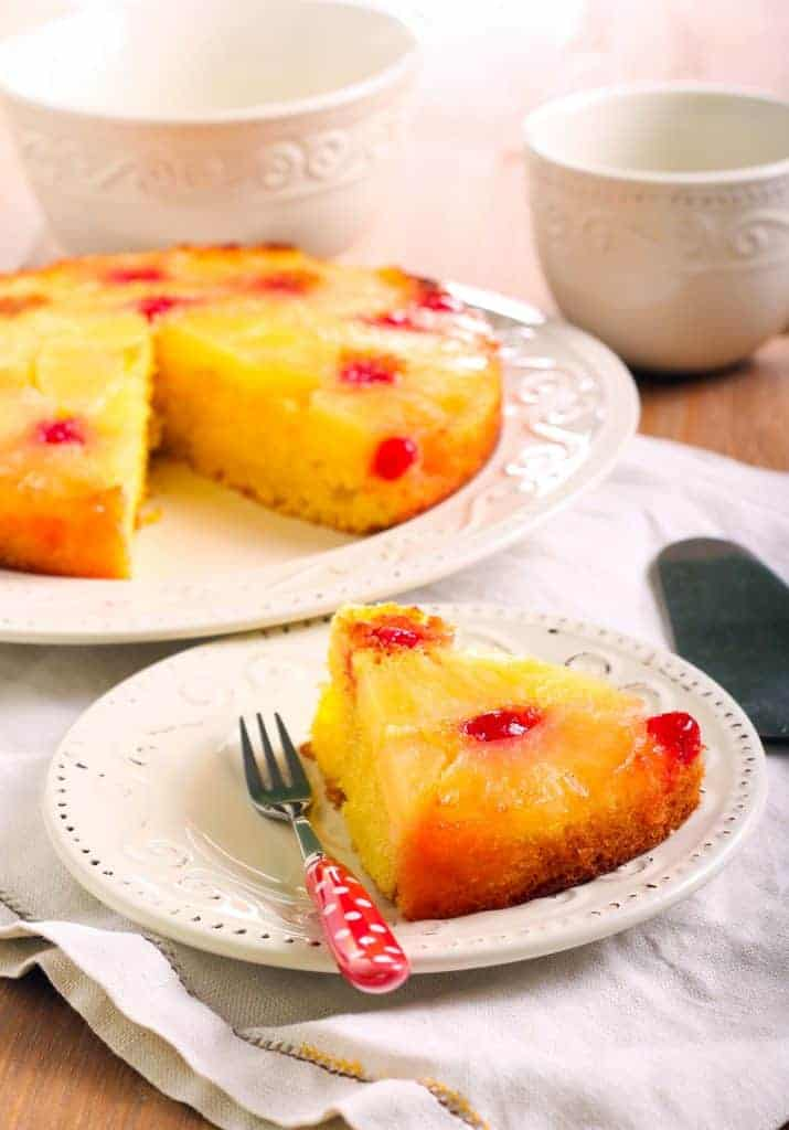 Pineapple upside down cake on a plate with pineapples and cherries on top.