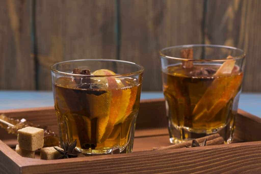 Photograph of hot apple cider spiked with rum. Short cocktail glasses filled with the cocktail and sliced apples and cinnamon sticks.