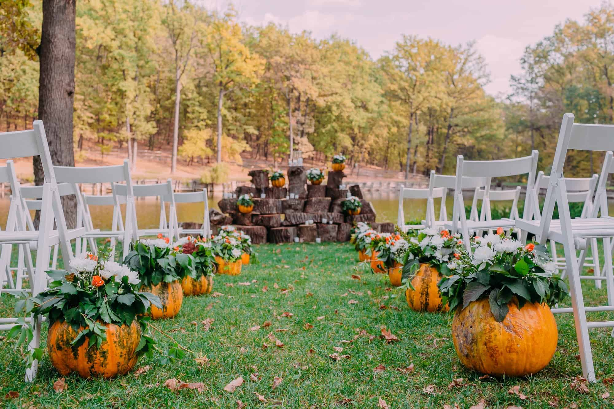 A fall wedding with white folding chairs set up outside with pumpkins at the end of every aisle.