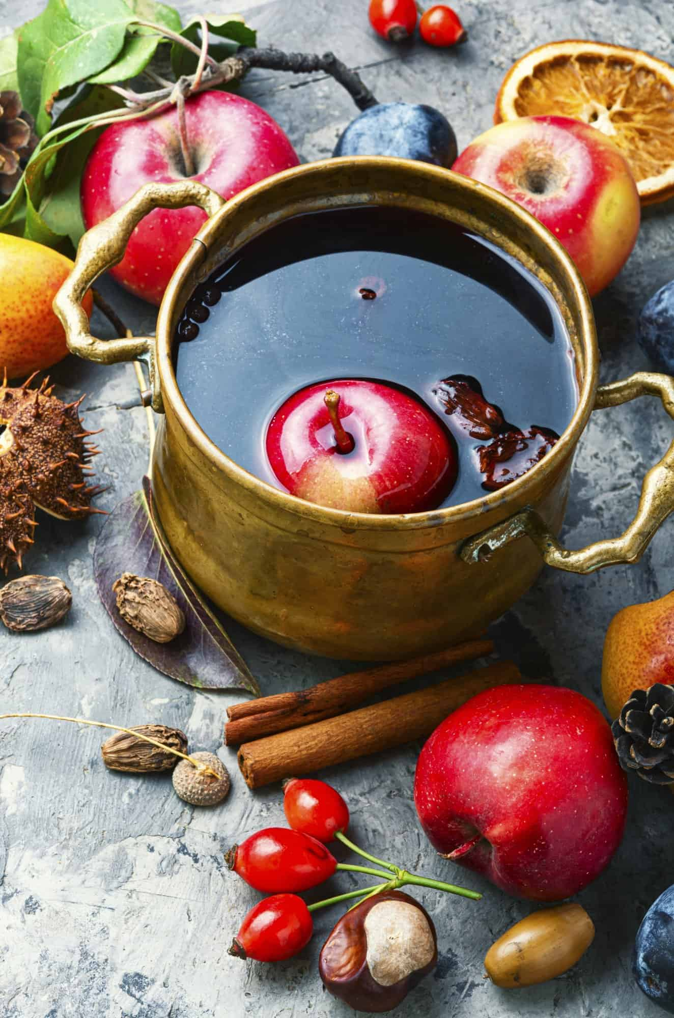A copper pot with mulled wine surrounded by apples and cinnamon.